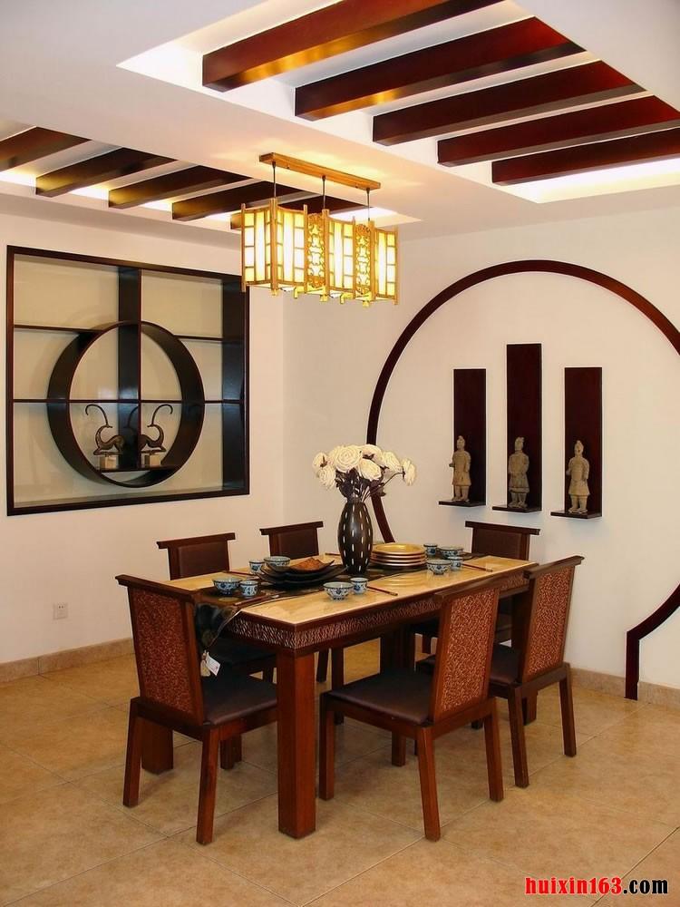 在餐厅的顶面上是两排漂亮优雅的有些复古气息的假木梁的设计,餐桌正上方有一组金黄色的漂亮的方形的宫灯,在靠近餐桌的墙面上还有三个壁龛,里面具有三个兵马俑的模型,组合搭配出非常非常古典和具有历史气息的装饰效果。